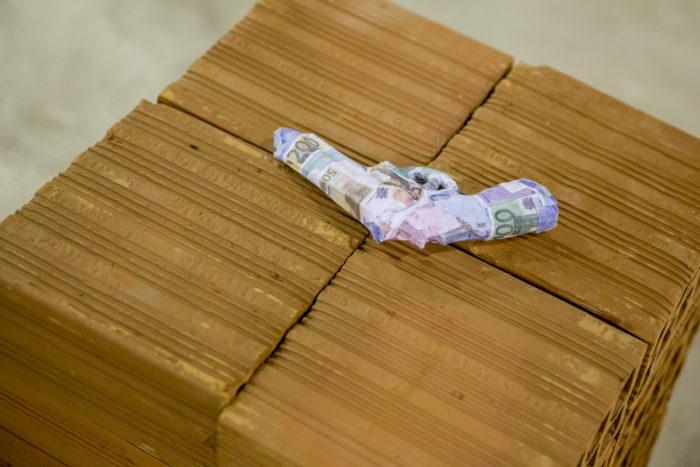 Bianka Mieskes, Its all about money, 2017, Waffe aus Spielgeld, Mauersteine, 62 cm x 39 cm x 38 cm